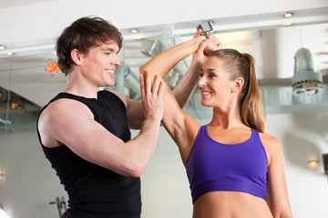 Paar trainiert in Fitnessstudio mit Hanteln