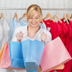 lachende frau schaut in einkaufstüte