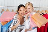 zwei freundinnen haben spaß beim einkaufen