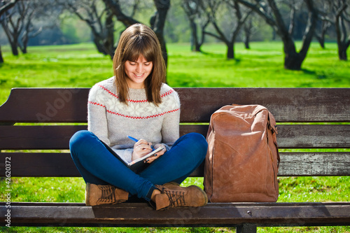 girl sitting in a park and doing her homework