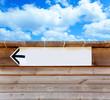 aged wood arrow direction sign on blue sky