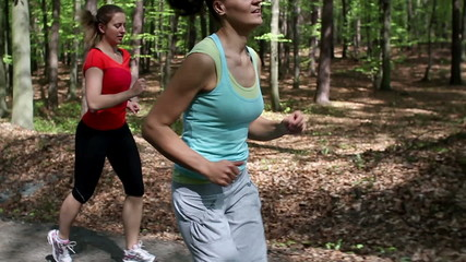 Two happy woman jogging in the forest, steadycam, slow motion
