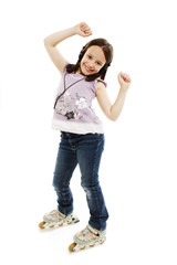 The beautiful little girl with earphones in roller skates