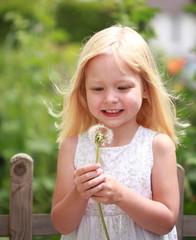 Mädchen freut sich über Pusteblume