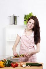 frau gibt gurken in eine schüssel mit salat