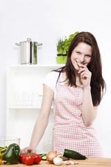 junge frau beim kochen nascht an einem stück gurke