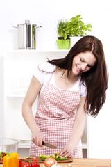 lachende junge frau in der küche schneidet grüne paprika