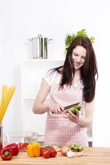 junge lachende frau in ihrer küche bereitet salat zu
