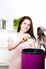 junge lachende frau in der küche entsorgt biomüll