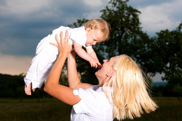 Mutter spielt mit Baby auf Wiese