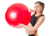 Pregnant  young woman and red fitness ball