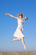 Attractive young woman in white sundress running