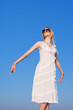 Young woman in white sundress  on background of sky