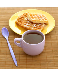 Sweet waffles on plate and cup of tea on table
