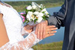 Hands and rings with wedding bouquet