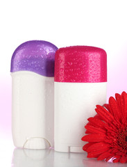 deodorants with flower on pink background