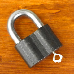 old padlock with key on wooden background close-up
