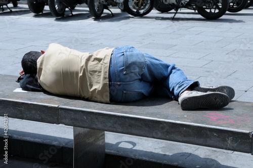 Uomo sdraiato su panchina