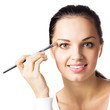 Woman applying eye shadow, by visage brush