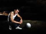 man with soccer ball staying on chapped soil poster