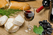 Red wine, Brie and Camembert cheeses with bread on the table