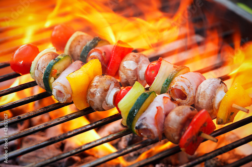 barbecue with flames and vegetable spit