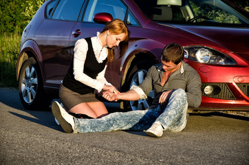 Young girl masures man's pulse on a road. First aid