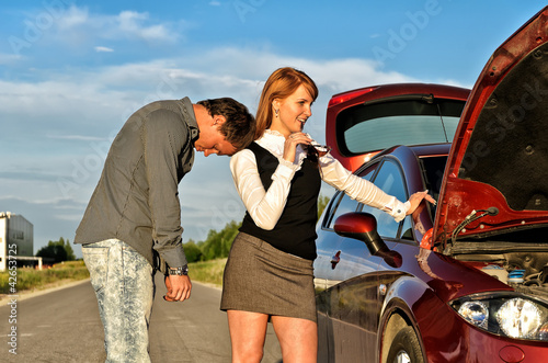 Tired man leaning to his gilfriend shoulder near broken car