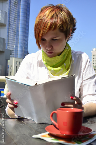 young woman in a cafe reading a book
