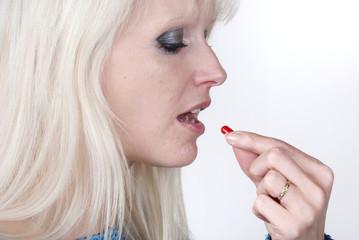 Woman holding a painkiller between finger