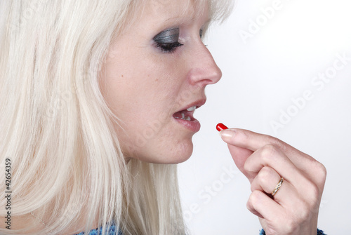 Woman holding a painkiller between finger