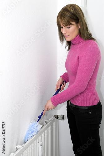 Frau wischt Staub hinter einer Heizung