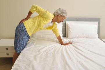 Frau verletzt beim Betten machen ihren  Rücken