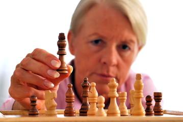 Ältere Frau beim Schach spielen