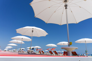 white beach umbrellas on Rimini beach, Italy
