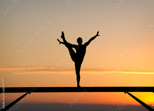 silhouette of female gymnast on balance beam in sunset - 42661349