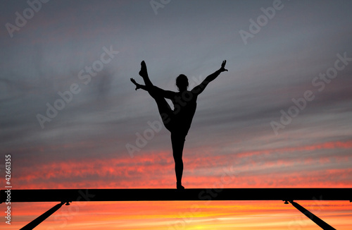 silhouette of female gymnast on balance beam in sunset