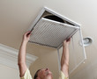 Leinwanddruck Bild - Senior man opening air conditioning filter in ceiling