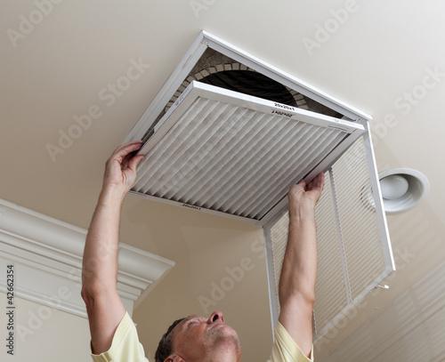 Leinwanddruck Bild Senior man opening air conditioning filter in ceiling