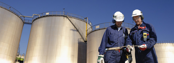 oil workers with storage towers in background