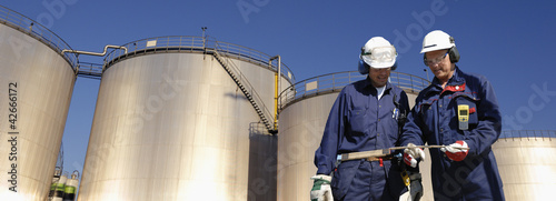 oil workers with storage towers in background - 42666172