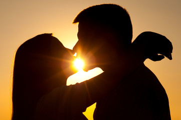 Silhouettes of young couple kissing on sunny summer day