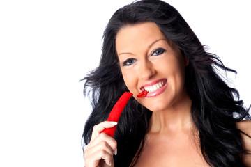Schöne junge Frau beißt in eine Chilischote
