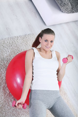 woman with dumb bells on exercise ball