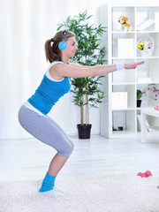 Sportive lady doing squatting at home