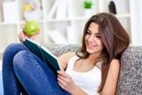 Adorable girl reading book at home