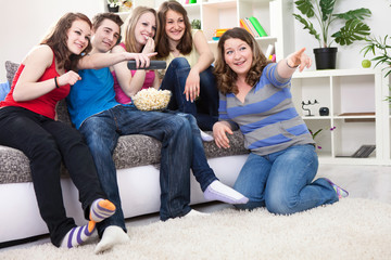 Young people laughing and watching TV