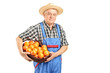 A male farmer holding a basket full of oranges