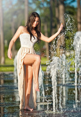 young beautiful brunette girl playing at outdoor water fountain