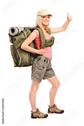 Full length portrait of a female hiker with backpack giving a th